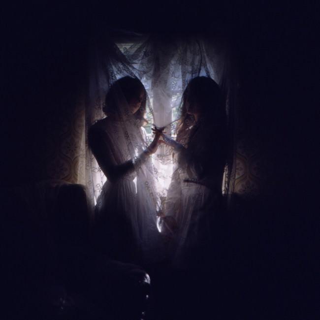 zwei Mädchen hinter einer Gardine.