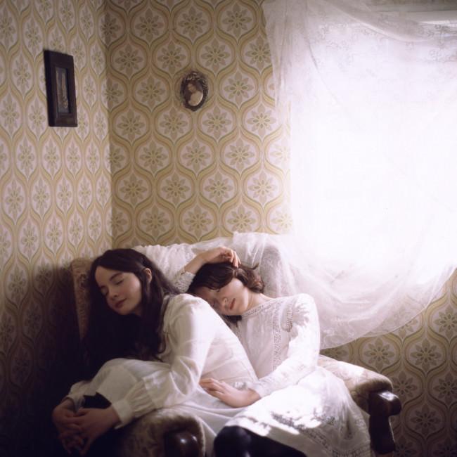 Zwei Mädchen sitzen auf einem Sessel und schlafen.