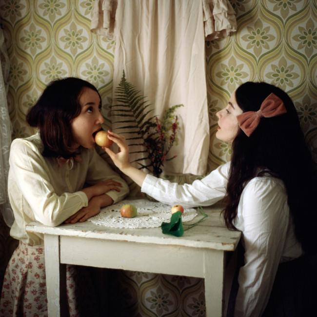 Ein Mädchen füttert das andere Mädchen mit einem Apfel.