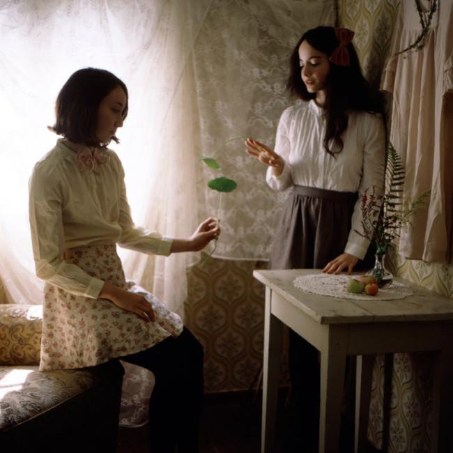Zwei Mädchen stehen in einem Raum und erzählen sich etwas.