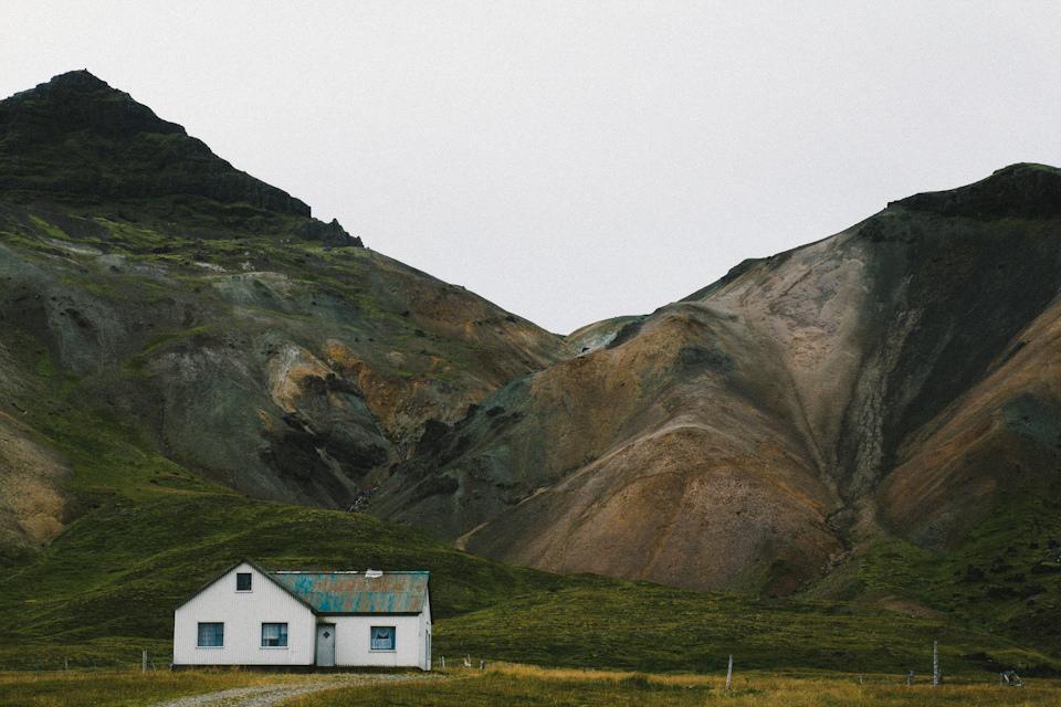 Ein Haus vor einem Hügel.