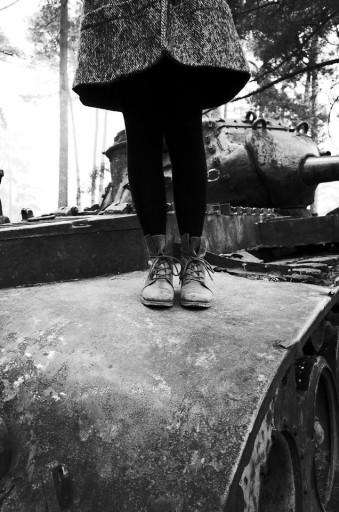 Eine Frau steht auf einem Panzer.