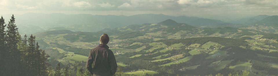 Ein Mann steht vor einer Landschaft und genießt den Ausblick.