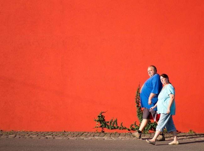 Ein Mann und eine Frau gehen vor einer knallroten Wand mit etwas Efeu vorüber.
