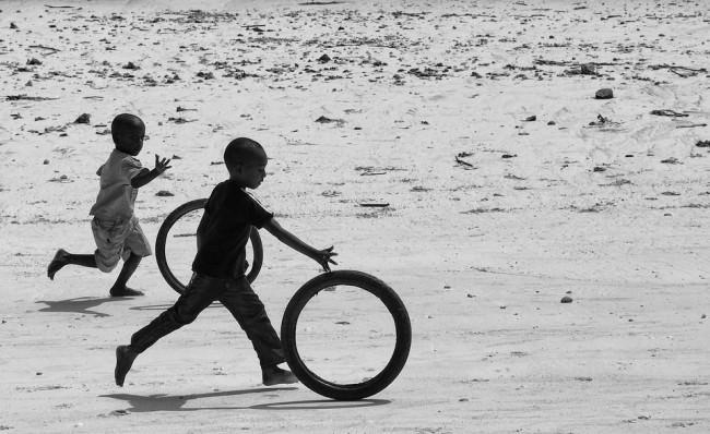 Zwei Jungen spielen mit zwei Reifen am Strand.