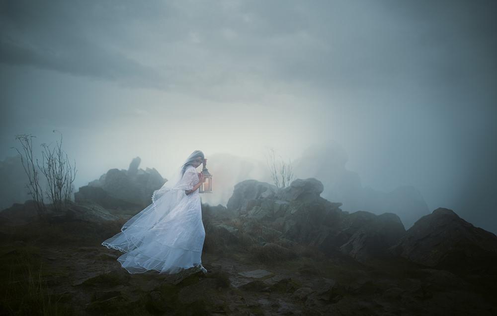 Frau mit Laterne in nebliger Landschaft.