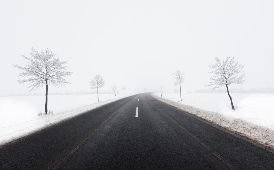 Dunkle Straße führt durch eine verschneite Winterlandschaft