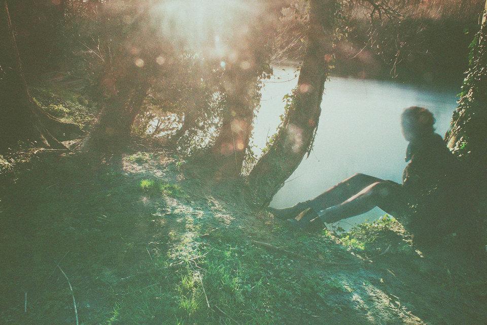 Jemand sitzt am Fluss und schaut raus.