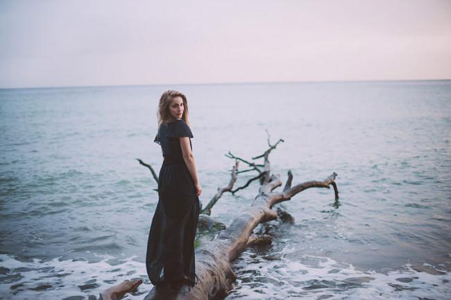 Eine Frau steht auf einem Baum am Wasser