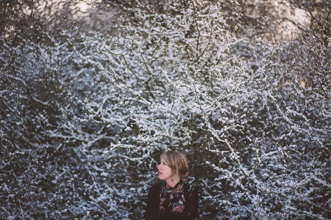 Eine Frau vor einem verschneiten Busch