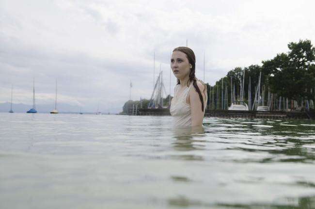 Ein fröstelndes Mädchen steht nass im Wasser.