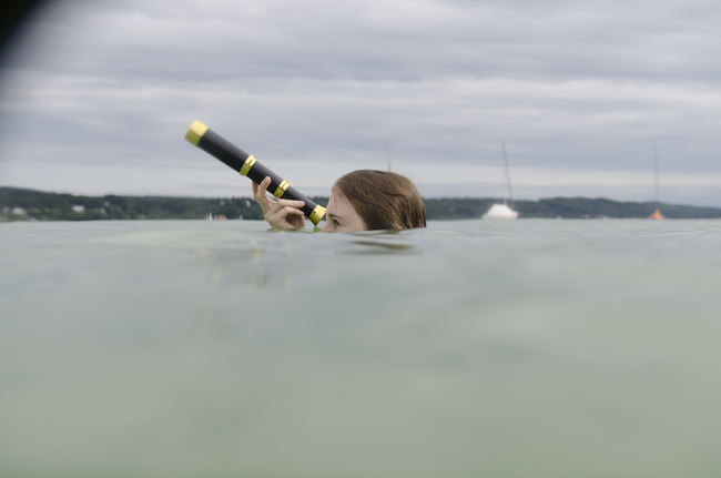 Eine Frau schaut mit einem Fernglas aus dem Wasser