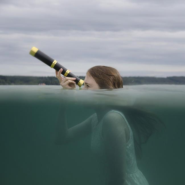 Eine Frau schaut mit einem Fernglas aus blauem Wasser