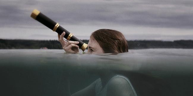 Ein Mädchen durchbricht die Wasseroberfläche mit ihrem Fernrohr.
