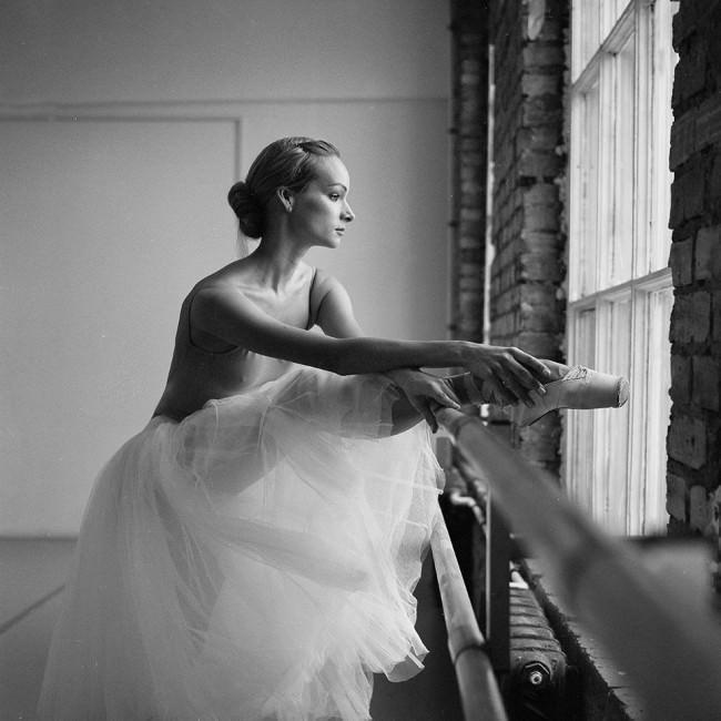 Eine Tänzerin hält ihr Bein auf einer Stange am Fenster.