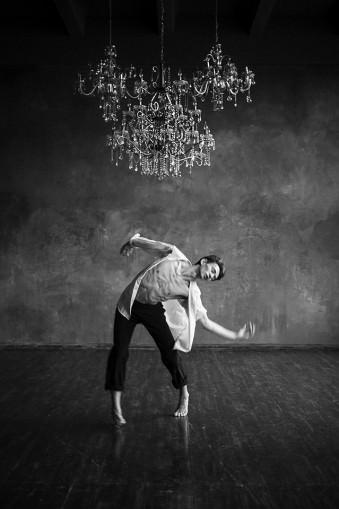 Ein Mann tanzt unter einem Kronleuchter.