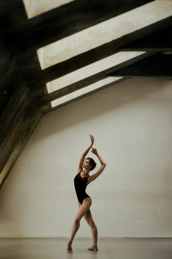 Eine Tänzerin unter Schrägfenstern.