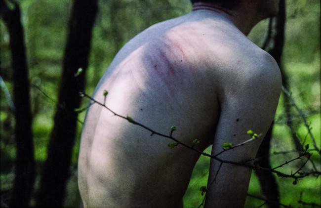 Der Rücken eines Mannes mit blutigen Striemen auf dem Rücken.