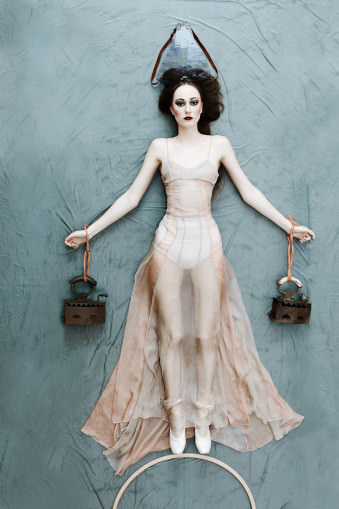 Eine Frau liegt auf dem Rücken und schaut in die Kamera in einem fast durchsichtigem Kleid.