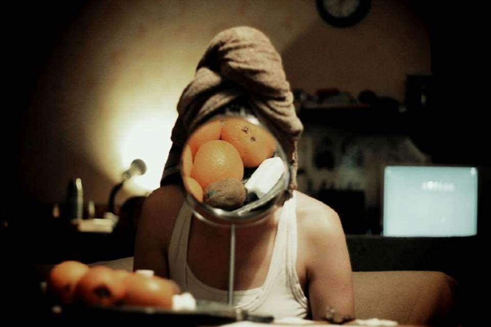 Ein Spiegel vor dem Gesicht einer Frau zeigt Mandarinen.