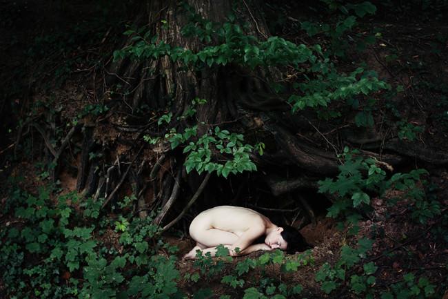 Eine Frau liegt unter einer Wurzel.