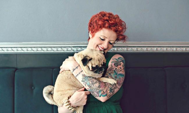 Eine Frau mit Hund auf dem Arm