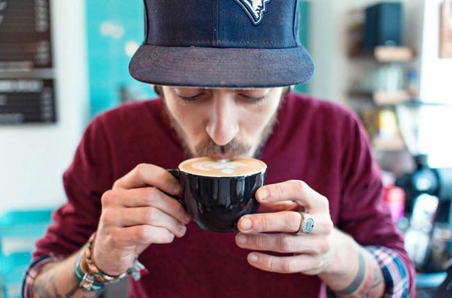 Ein Mann trinkt aus einer Tasse.