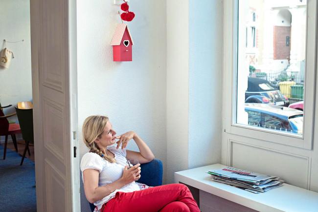 Eine Frau sitzt auf einem Stuhl und sieht aus dem Fenster.