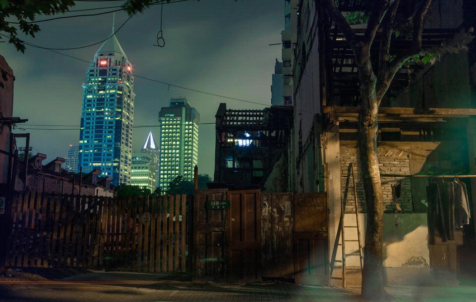 Ein dunkler Zaun, im Hintergrund Hochhäuser.