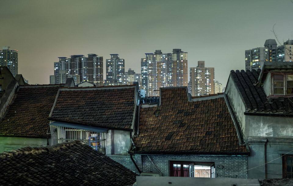 Einfache Häuser vor Hochhäusern im Hintergrund.