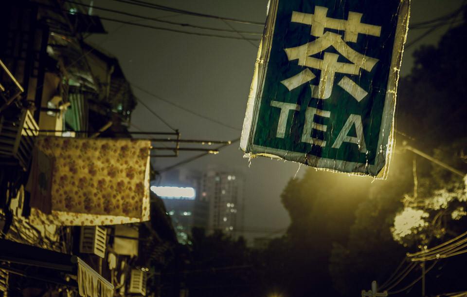 Eine dunkle Straße mit Tee-Schild.