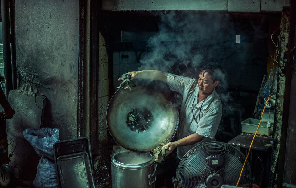 Mann mit dampfenden Wok.