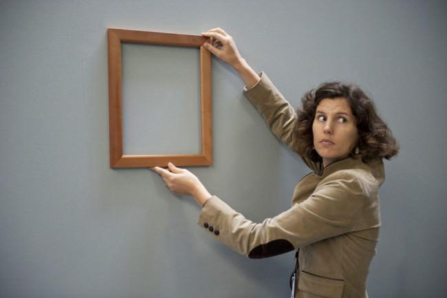 Eine Frau hält einen Bilderrahmen an die Wand.
