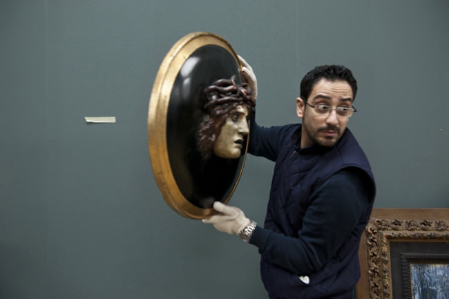Ein Mann hält ein Bild, aus dem ein Mann schaut.