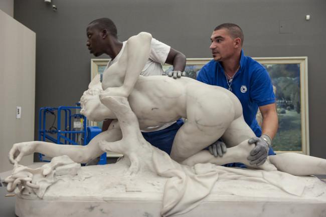 Zwei Männer tragen eine Statue.