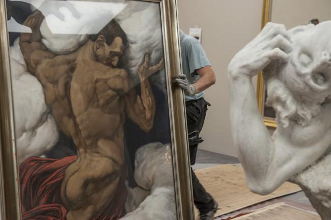 Männer tragen ein Gemälde.
