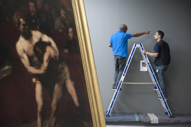 Zwei Männer auf der Leiter und ein Gemälde mit kämpfenden Männern.