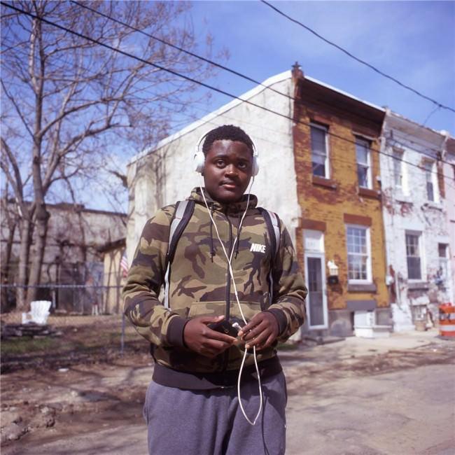 Ein Junge mit Kopfhörern auf der Straße.