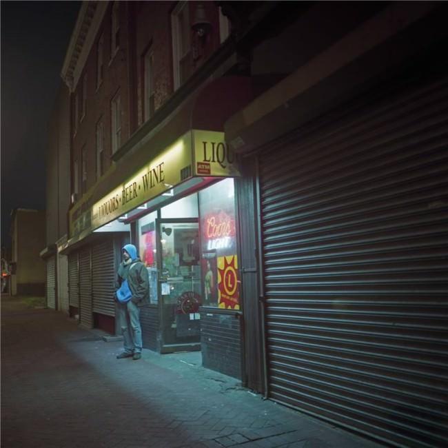 Ein Mann steht nachts vor einem Laden.
