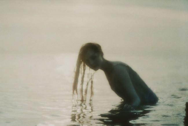 Eine Frau im Wasser schaut zu uns.