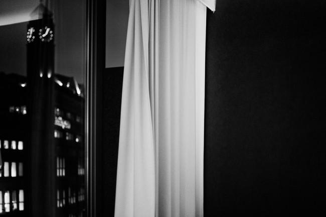 Blick aus einem Hotelfenster, im Vordergrund ein heller Vorhang, draußen Nacht