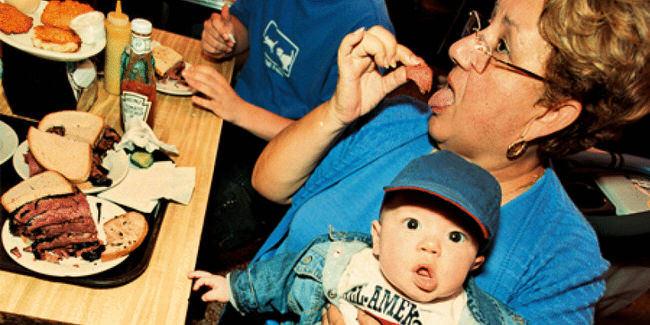 Eine Frau sitzt mit einem Jungen am Tisch und isst.