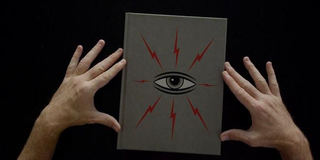 Zwei Hände fassen ein Buch mit einem Auge darauf.