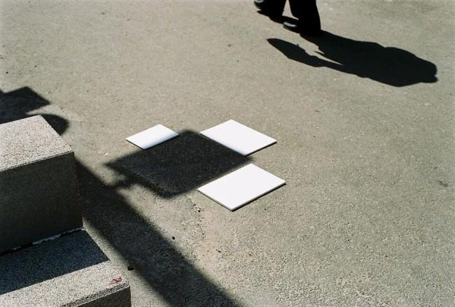 Weiße Fliesen liegen um ein Schattenquadrat herum.