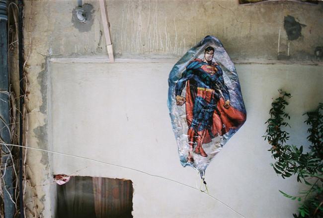 Ein luftleerer Balon mit Superman-Aufdruck hängt an der Wand.