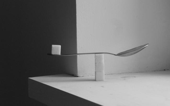 Ein Zuckerwürfel balanciert auf einer Löffelkonstruktion.
