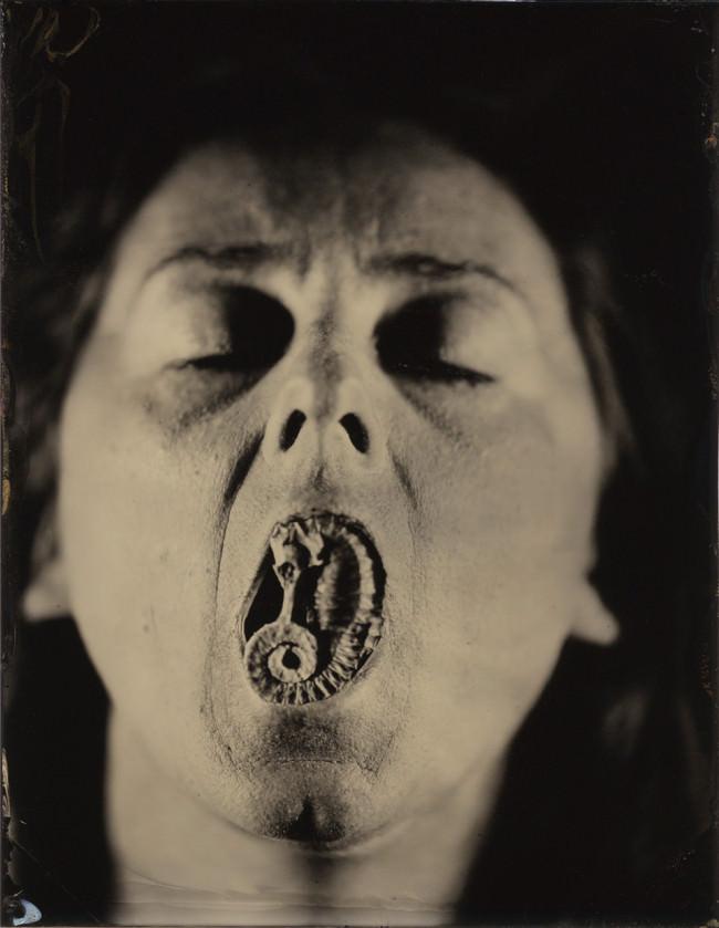 Eine Frau hat etwas im Mund und die Augen dabei geschlossen.