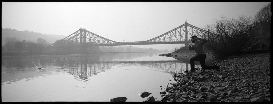 Portrait in der Landschaft: Ein Mann wirft einen Stein in einen Fluss, im HIntergrund ist eine Brücke zu sehen.
