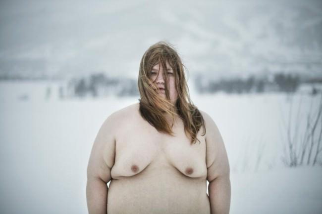 Eine nackte Frau steht in einer Schneelandschaft.