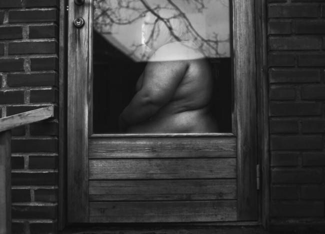 Nackte Frau steht hinter einem Fenster.